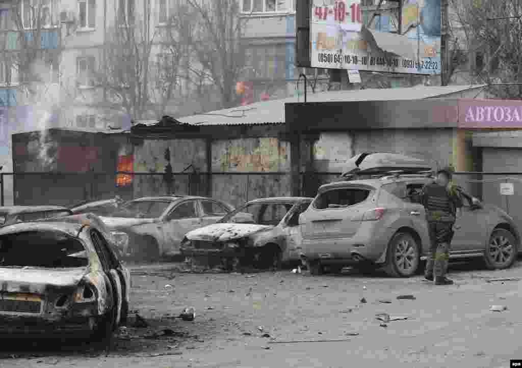 Военнослужащий украинской армии осматривает поврежденный автомобиль