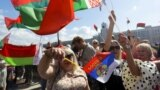 BELARUS – Supporters of Belarusian President Alexander Lukashenko hold Belarusian State Flags, as some of them wave a Russian national flag during a rally at Independent Square of Minsk, August 16, 2020