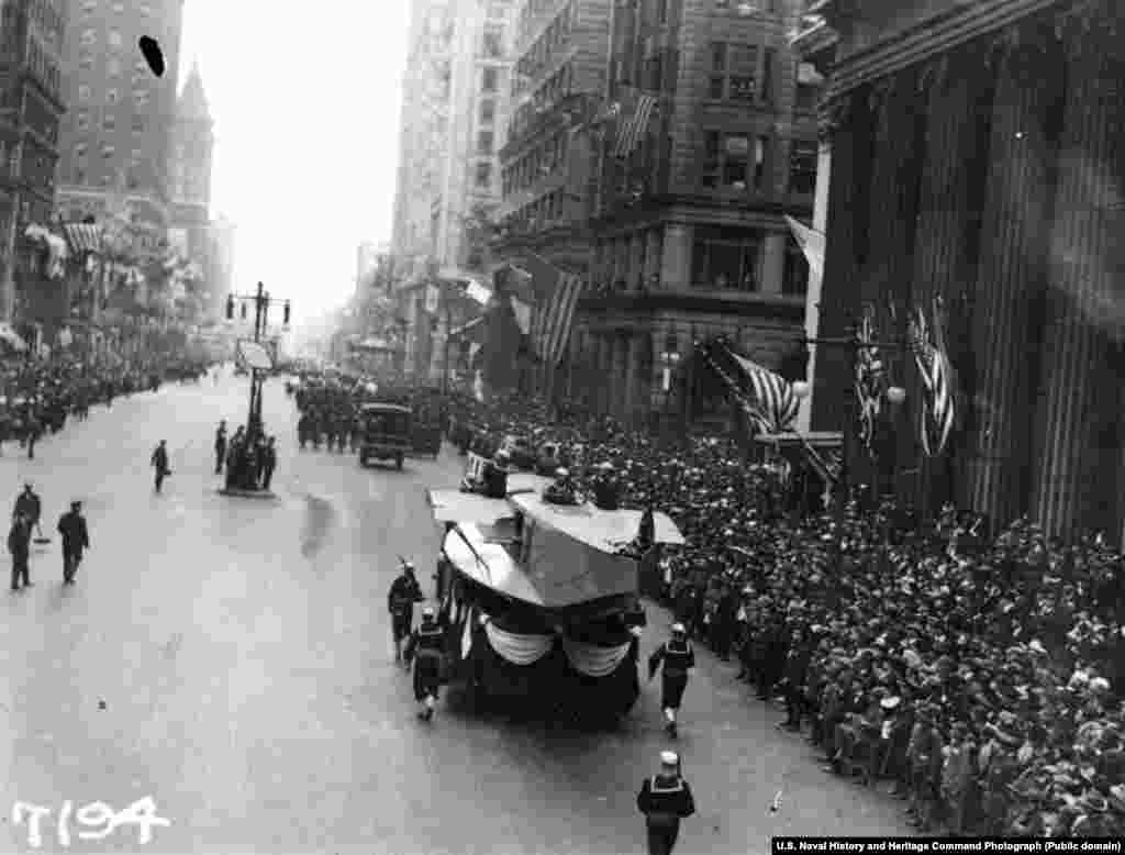 Мобильный стенд завода морской авиации движется по Широкой улице Филадельфии во время парада, посвященного Закону о займах свободы. Займы свободы – облигации, которые выпустило правительство США, чтобы оплатить расходы на войска коалиции во время Первой мировой войны. Парад прошел 28 сентября 1918 года. За день до парада в Филадельфии 118 человек были больны испанкой