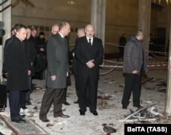 Лукашенко в окружении сотрудников службы безопасности осматривает место взрыва в минском метро 12 апреля 2011 года