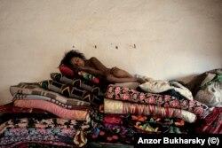 Девочка из деревни ромов спит на горе из перин и одеял. 2010