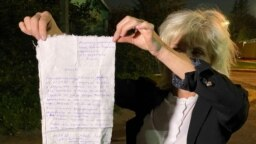 """Lawyer Lyudmila Kazak holds up a complaint that one of her clients wrote and handed over to her in Minsk on September 25. Kazak herself was abducted and later found guilty of """"failing to obey"""" police at an opposition rally that she says she didn't even attend."""