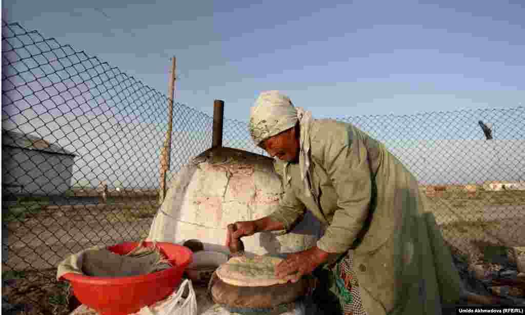 Женщина закладывает лепешки в тандырную печь в селе, где живут верблюдоводы.