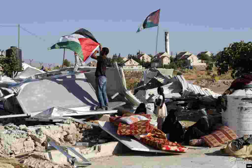 """Как рассказали жители """"самостроев"""", армия сносит их дома уже в девятый раз. На фото – мужчина устанавливает палестинский флаг на обломках своего дома"""