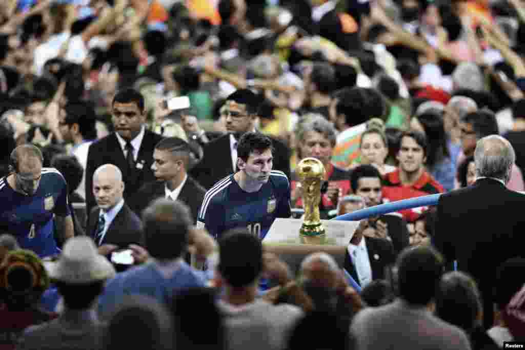 """В категории """"Спорт. Одиночные снимки"""" победу одержал китайский фотограф Бао Тайлян - с фотографией аргентинской футбольной звезды Лионеля Месси, рассматривающего Кубок мира во время заключительной церемонии прошлогоднего мирового первенства в Бразилии."""