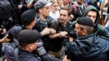 RUSSIA -- Opposition activists clash with police as they attend a rally against efforts to stop opposition candidates to register for the elections to the Moscow City Duma during a march in central Moscowm July 14, 2019