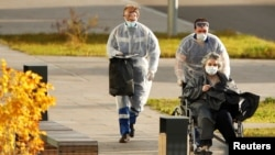 Medical workers push a woman in a wheelchair outside a hospital for patients infected with COVID-19 on the outskirts of Moscow on October 15, 2020.