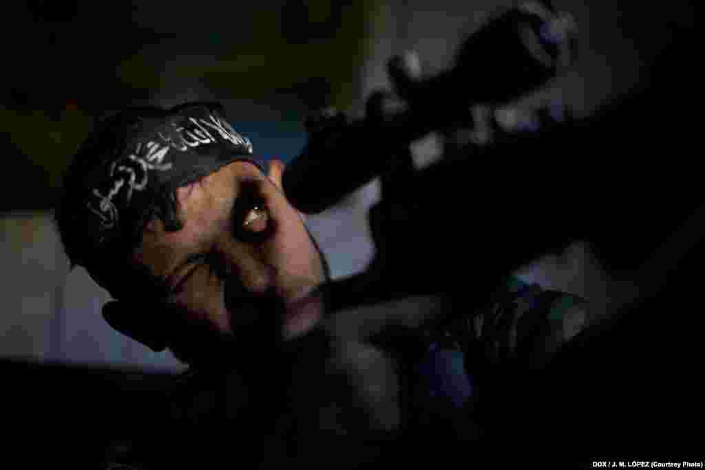 30-летний Абу Суфьен высматривает цель из одного из разрушеных зданий в сирийском городе Алеппо 30 декабря 2012 года. Несмотря на перемирие, в Алеппо до сих пор идут бои. Многие его жители уже давно покинули город и бежали в более безопасные места