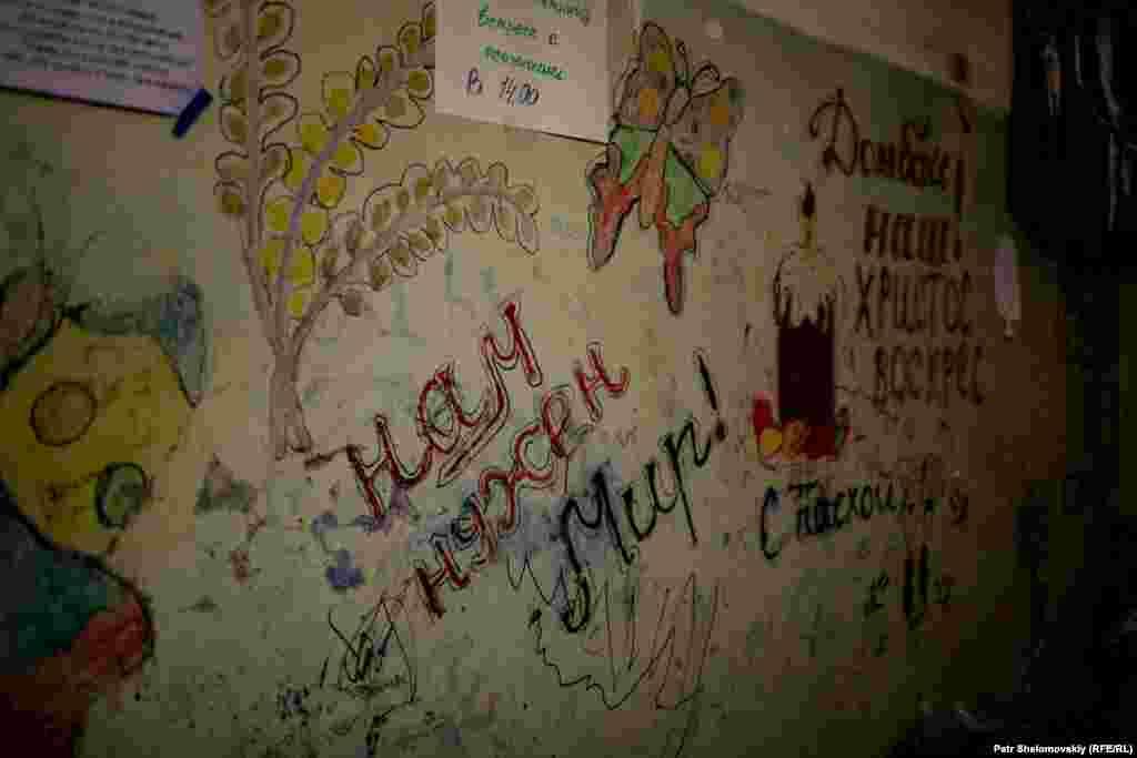 Пока звуки падающих снарядов еще доносятся с улицы, дети разрисовывают стены своего временного жилища надписями, призывающими к миру