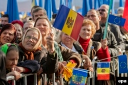 People wave flags at a 2013 demonstration in the Moldovan capital, Chisinau, to support Moldova receiving an Association Agreement with the European Union.