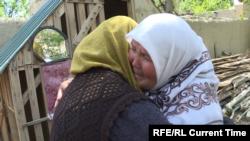 Women embrace in the Tajik village of Somoniyon while surveying damage to their houses following April 28-April 29, 2021 border fighting with Kyrgyzstan.