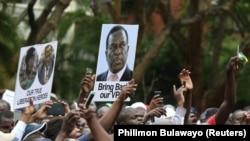 Участники демонстрации в Хараре держат плакаты в поддержку опального вице-президента Зимбабве