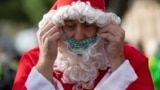 Spain - A swimmer in a Santa Claus costume prepares to participate in the 111th edition of the Copa Nadal (Christmas Cup) swimming race in Barcelona's Port Vell on December 25, 2020