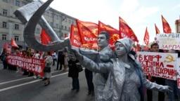 """Пара участвует в первомайском шествии в Москве, изображая памятник """"Рабочий и колхозница"""" работы Веры Мухиной. Фото: Reuters"""
