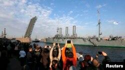 Крейсер буксируют в док в сентябре 2014 при большом стечении людей