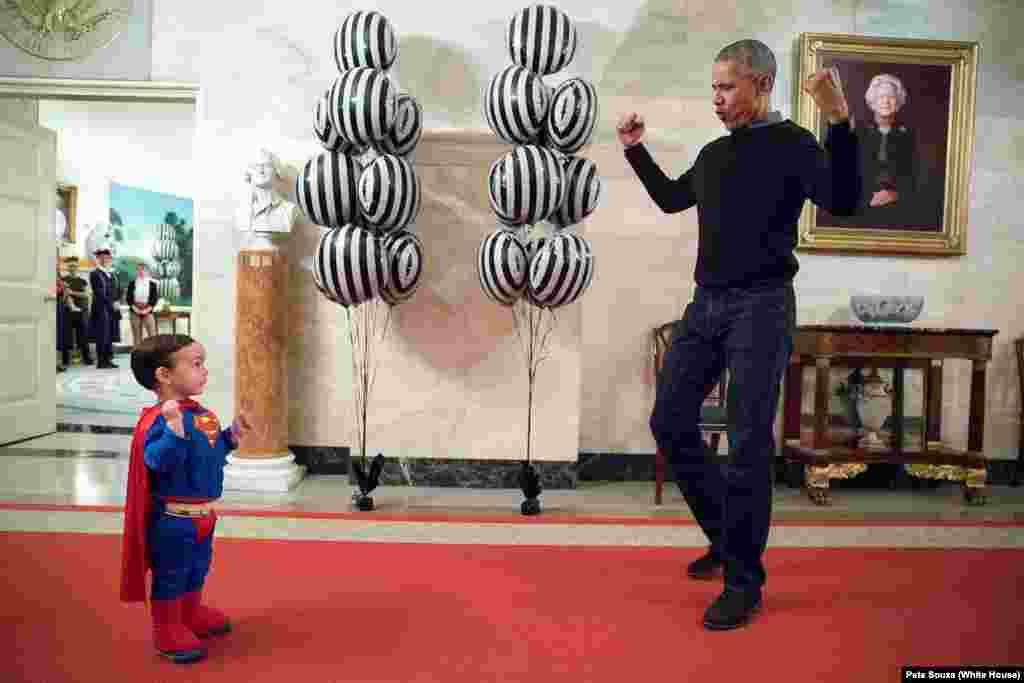 Маленький Уокер, сын пресс-секретаря Обамы Джоша Эрнеста, демонстрирует свой костюм президенту во время празднования Хэллоуина в Белом доме. 31 октября 2016 года.