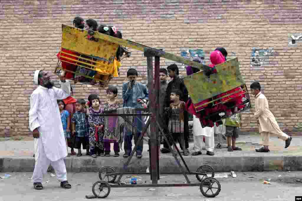 Дети на качелях в Пешаваре, Пакистан, во время празднования Ураза Байрам (epa/Bilawal Arbab)