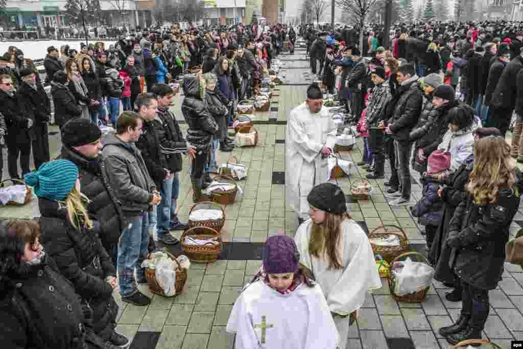 На фото – румынский католический священник благославляет корзины с едой на главной площади города Меркуря-Чук