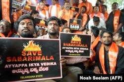 """Члены индуистского националистического движения держат плакаты с надписью """"Спасите Сабарималу"""". Ноябрь 2018"""