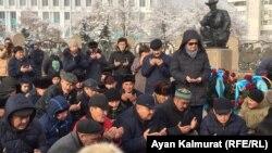 Собравшиеся у монумента Независимости в Алматы читают молитву в память о погибших в городе Жанаозене в 2011 году и выступлениях молодежи в декабре 1986 года