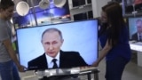 Russia -- Shop assistants install a TV set at a shop in Moscow during the broadcast of Russian President Vladimir Putin's annual state of the nation address, December 3, 2015