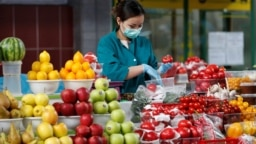Kazakhstan - vendor wearing a protective face mask following an outbreak of the coronavirus disease (COVID-19) pack vegetables at a local food market, also known as bazaar, in Almaty, Kazakhstan March 20, 2020. REUTERS/Pavel Mikheyev