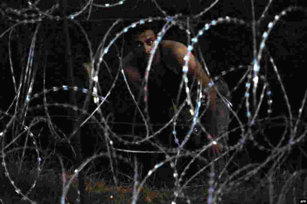 Мигрант за ограждением из колючей проволоки на венгерско-сербской границе