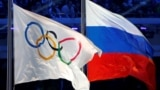 RUSSIA -- The Russian national flag (R) and the Olympic flag are seen during the closing ceremony for the 2014 Sochi Winter Olympics, Russia, February 23, 2014.