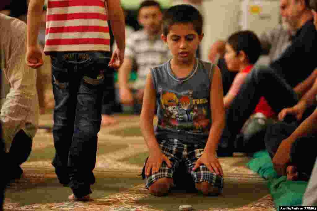 Накануне праздника Ураза-байрам верующие делают благотворительные приношения: продукты (в основном сухие сладости) или деньги, эквивалентные стоимости таких продуктов. Собранное идет малоимущим, странствующим На фото - мальчик на молитве в мечети в Баку