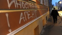 """RUSSIA -- MOSCOW, NOVEMBER 21, 2012. A bilingual graffiti message reading """"Foreign [intelligence] agent. Love USA"""" at the entrance to the offices of human rights group Memorial, in central Moscow."""