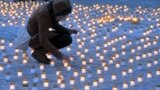 Estonia -- file -- A woman lights candles during a gathering in memory of Estonians deported to Siberia after the Soviet Union invasion in 1949, on March 25, 2011 in Tallinn