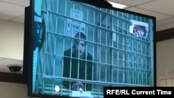 Pavel Ustinov appears on a video monitor during his hearing in a Moscow courtroom on September 20.