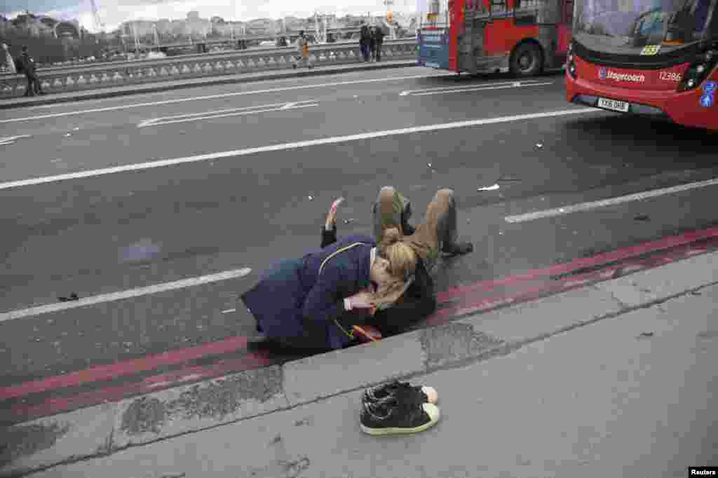 Женщина помогает раненому на Вестминстерском мосту