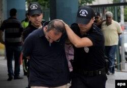 Полицейский арестовывает военнослужашего, подозреваемого в участии в перевороте 19 июля 2016