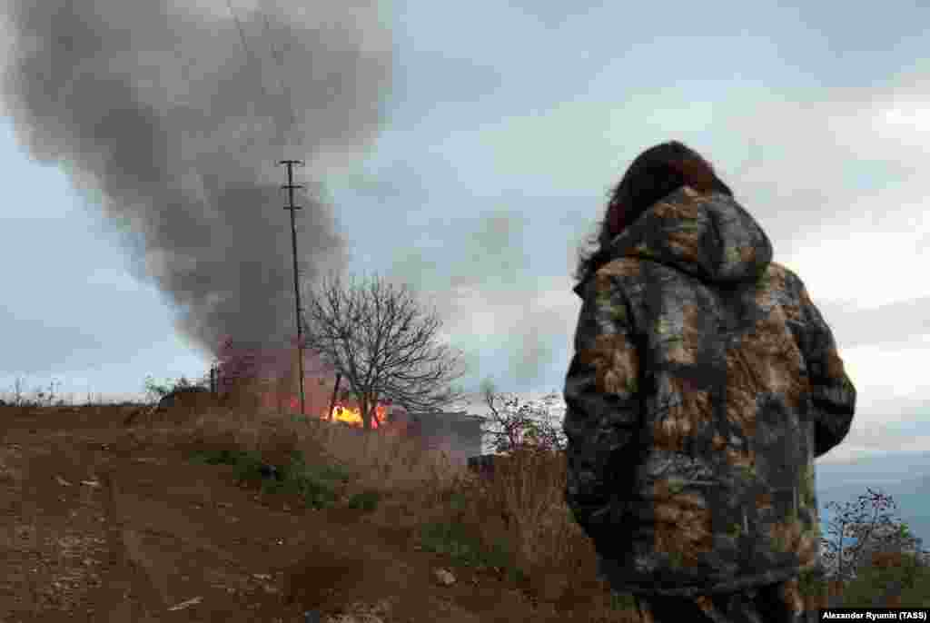 """A local resident watches a burning house in the town of Lachin (Berdzor) on November 30, 2020, the day before the town returned to Azerbaijani control. Another town resident told Agence France Presse that he had no intention of leaving: """"People live on both sides of borders after wars, and things are fine,"""" said the man, a grocery-store owner."""
