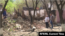 Komil Muminov stands by the ruins of his neighbor's house in the Tajik village of Somoniyon.