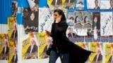 IRAN -- An Iranian woman walks past electoral posters during the last day of election campaign, in Tehran, February 19, 2020