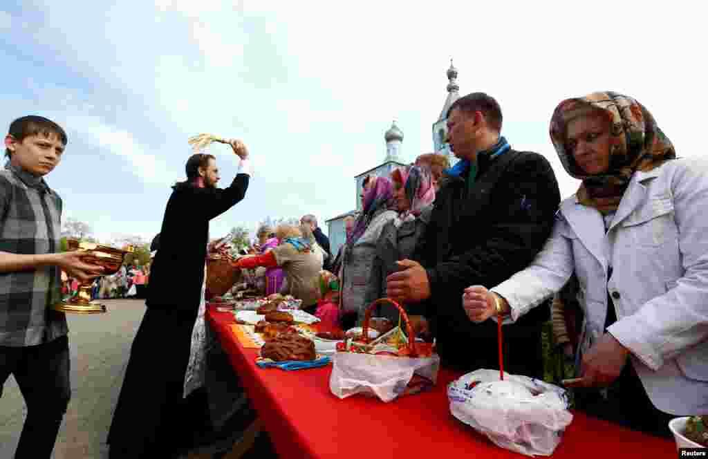 В течение Великой субботы, предшествующей Пасхе, принято освящать куличи, пасху, крашенки и другие продукты На фото – церковный служитель освящает еду прихожан. Бобруйск, Беларусь