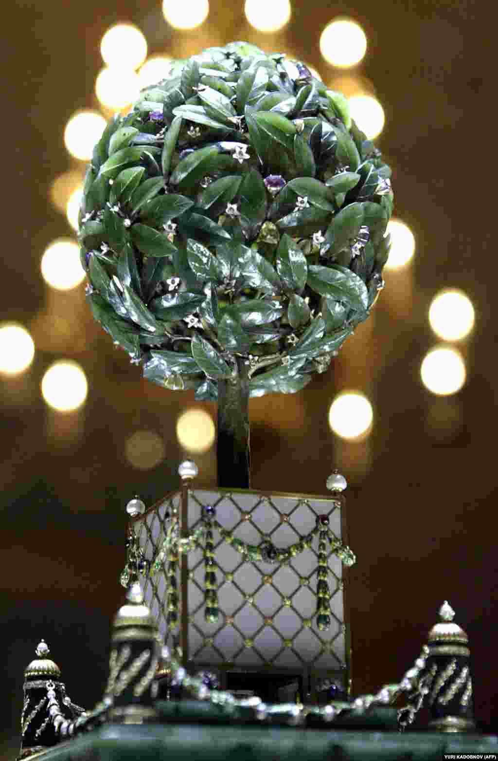 """Яйцо """"Лавровое дерево"""" создано в 1911 году. Один из бриллиантовых """"плодов"""" дерева, приводит в действие помещенный внутрь яйца """"сюрприз"""" –крошечную птицу, которая поднимается с вершины дерева, машет крыльями и поет. Через три года после того, как это яйцо было преподнесено в дар, Россия вступила в Первую мировую войну."""