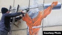 """Рабочие """"зачищают"""" граффити с распятым космонавтом в Перми"""