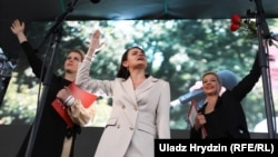 Belarusian presidential candidate Svyatlana Tsikhanouskaya, flanked by allies Veranika Tsapkala (left) and Maryya Kalesnikava, addresses her July 30 rally in Minsk.