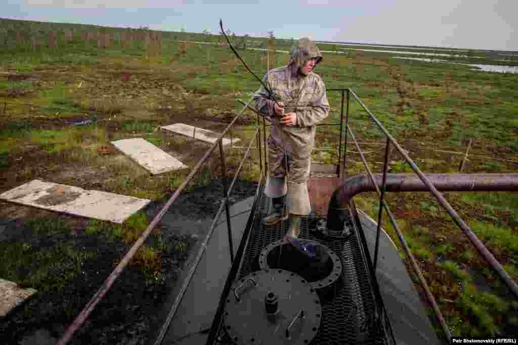 Сергей Мултанов измеряет уровень нефти в заброшенной нефтяной скважине