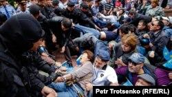 Полицейские задерживают людей на площади в центре Алматы, 9 июня 2019