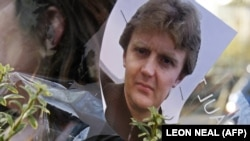 A picture of former Russian spy Aleksandr Litvinenko is pinned to flowers outside the University College Hospital in central London in November 2007.