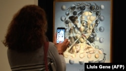 "A visitor takes a picture with his smatphone at the painting ""Gala lacidia,1952"" by artist Salvador Dali"