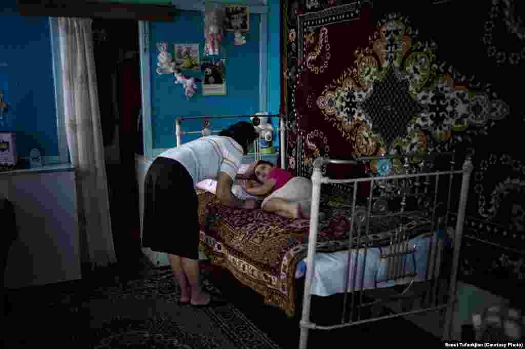 Мать ласкает свою 5-летнюю дочь в селе Мясникян, в бедной Армавирской области Армении. Семья борется с последствиями ряда несчастных случаев, в том числе укуса змеи и удара молнии. Многие жители Армавира получают помощь от диаспоральных организаций, таких как Фонд «Дети Армении».