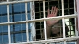 RUSSIA -- ITAR-TASS: VLADIMIR REGION, RUSSIA. JUNE 26, 2013. An inmate waves from a barred window at Prison No.2 in Vladimir Retion, operated by the Administration of the Federal Service of Execution of Punishments (UFSIN). (Photo ITAR-TASS / Stanislav Kr