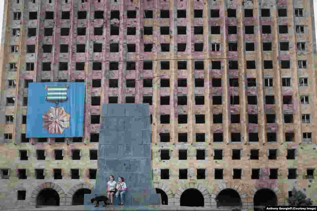 Девочки с собакой на фоне заброшенного административного здания советских времен в центре Сухуми. Здесь в 1992-93 годах шли наиболее ожесточенные бои.