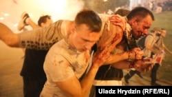 Люди несут раненого во время столкновений с силовиками. 9 августа