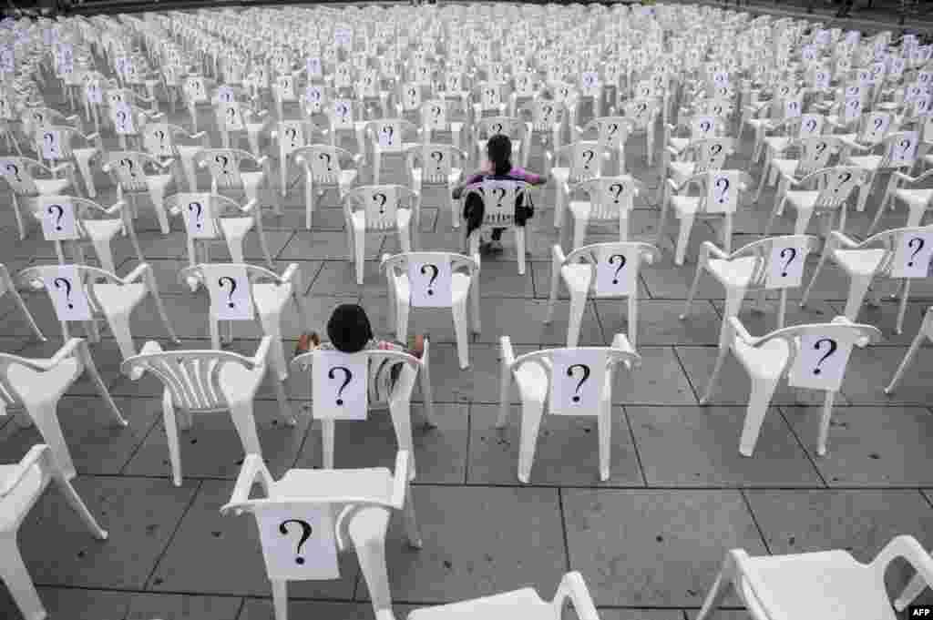 Дети на креслах с вопросительными знаками в Приштине, Косово, 30 августа, в Международный день пропавших без вести.